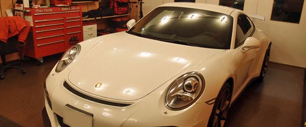 ポルシェのような車高の低い車が作業スペースに入っている写真画像、画像の車はポルシェ、911GT3