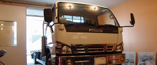 いすゞのエルフのような背も高く長い車両が作業スペースに入っている写真画像、画像のトラック車はいすゞ、エルフ